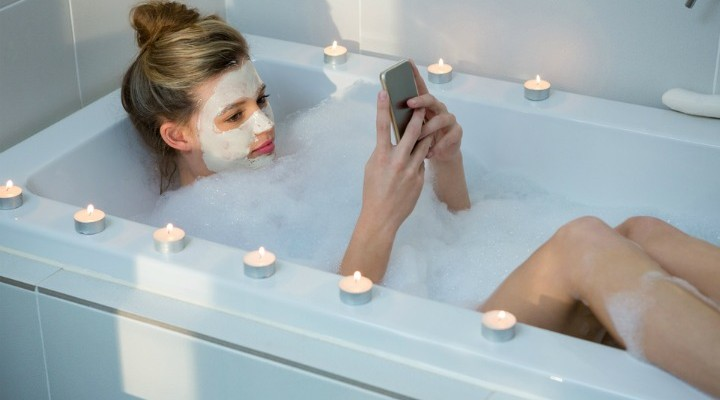 Woman using a Phone in the Bath - Soakology Blog